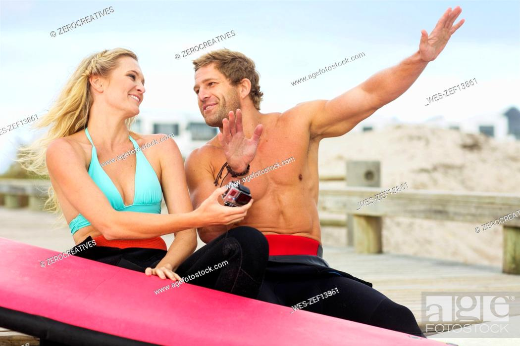 Stock Photo: Happy couple with surfboard talking on the beach.