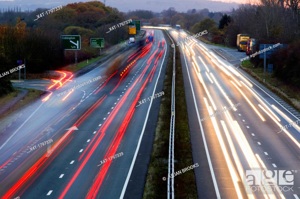 Stock Photo: traffic on a main road leaving light trails at dusk.