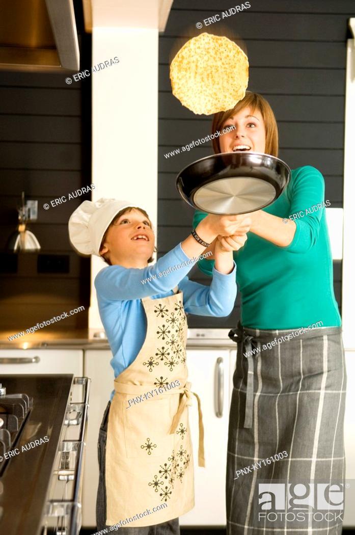 Stock Photo: Young woman flipping a pancake with her son.