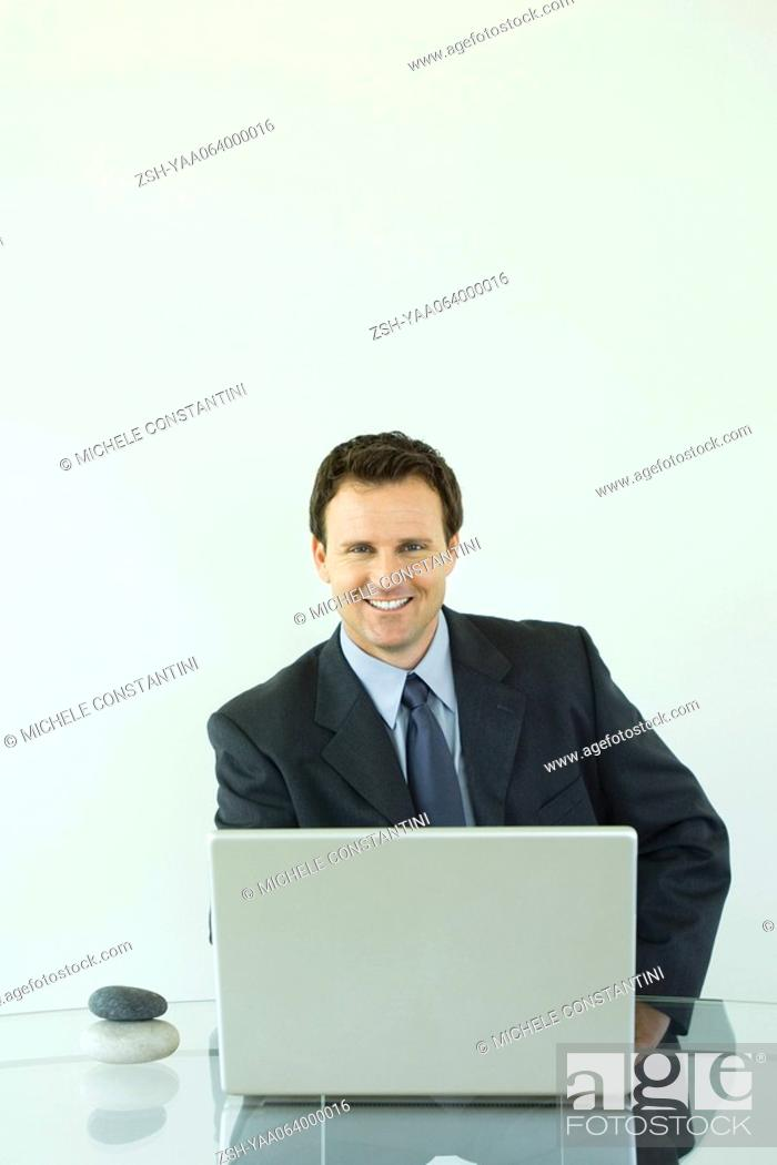 Stock Photo: Businessman using laptop computer, smiling at camera, pebbles stacked on desk next to him.