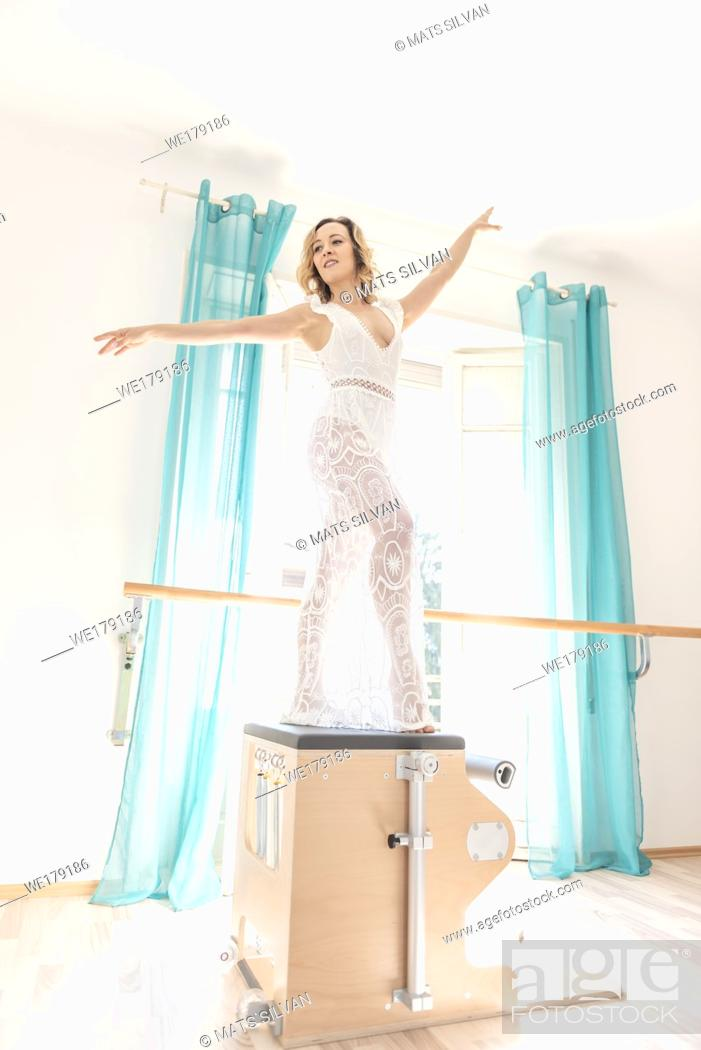 Stock Photo: Woman Exercising on Pilates Machine Against a Window With Sunlight in Switzerland.