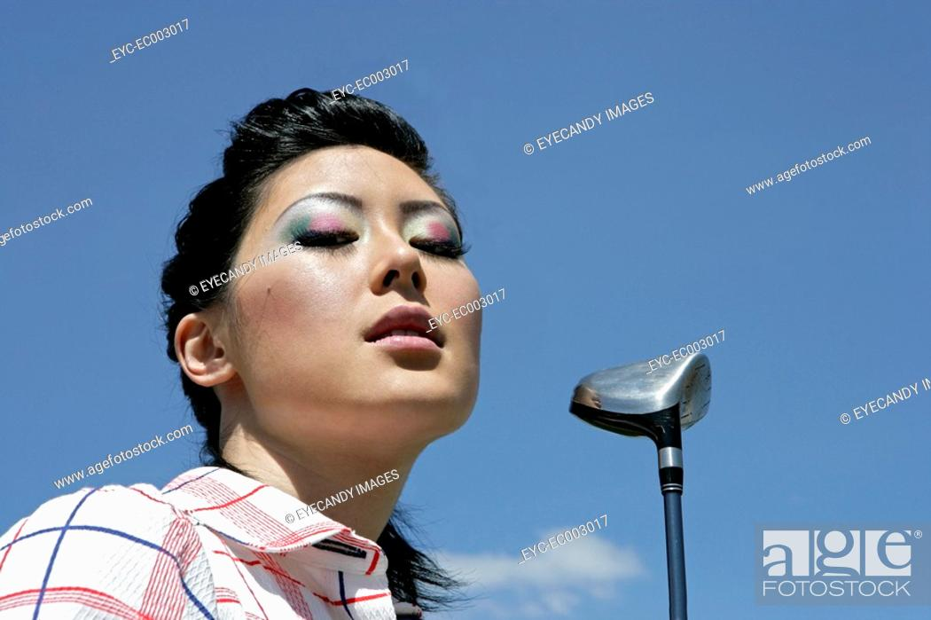 Stock Photo: Portrait of a young woman with a golf club.
