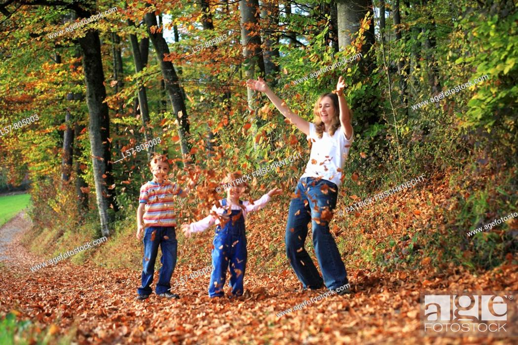 Stock Photo: Mother with daughter and son playing with leaves in fall, having fun, autumn foliage covering path in forest, autumn, fall, Zuerich, Switzerland.