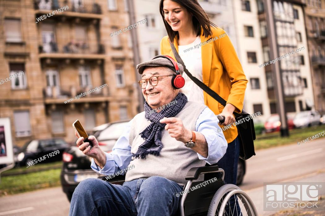 Photo de stock: Laughing young woman pushing happy senior man with headphones and smartphone in wheelchair.
