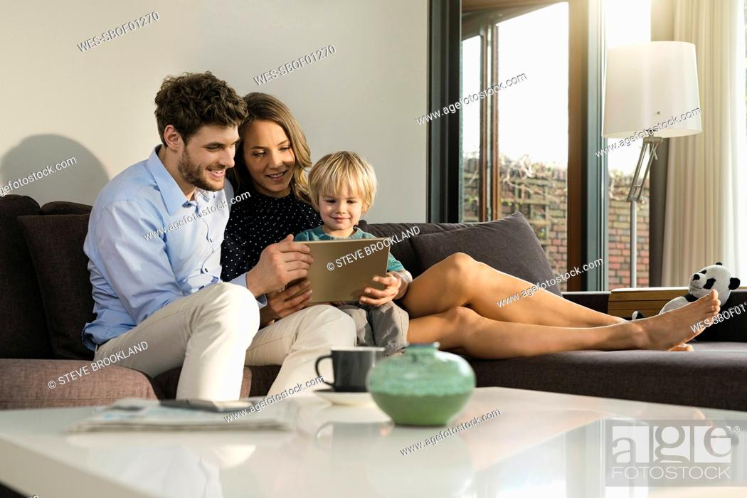 Stock Photo: Parents and son sitting on sofa holding tablet at home.