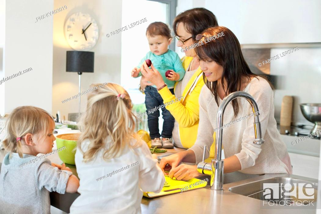 Stock Photo: Girls with her mother and grandmother in a kitchen.