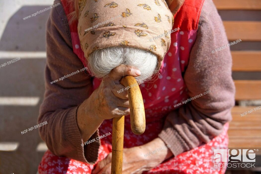 Stock Photo: old peasant woman sitting leaning on a walking stick.