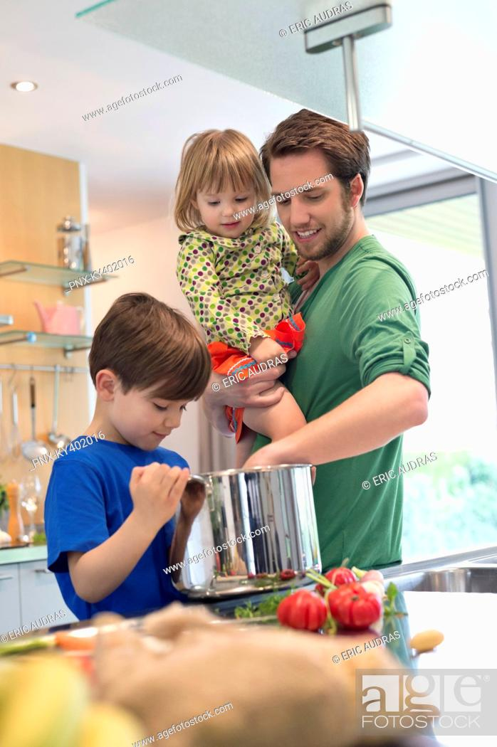 Stock Photo: Man with his son and daughter in the kitchen.