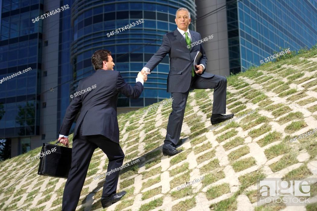 Stock Photo: One businessman is pulling up another on a hill.