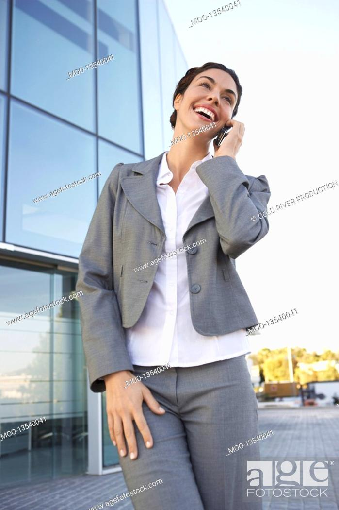 Stock Photo: Businesswoman talking on mobile phone in front of office building.