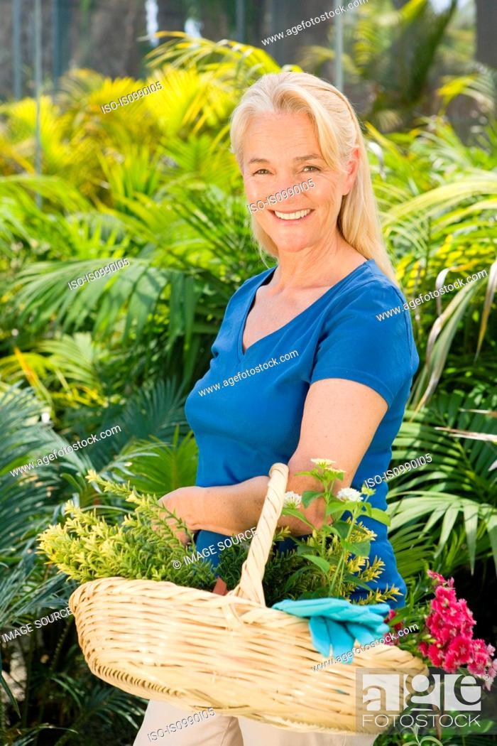Stock Photo: Mature woman amongst plants with basket.