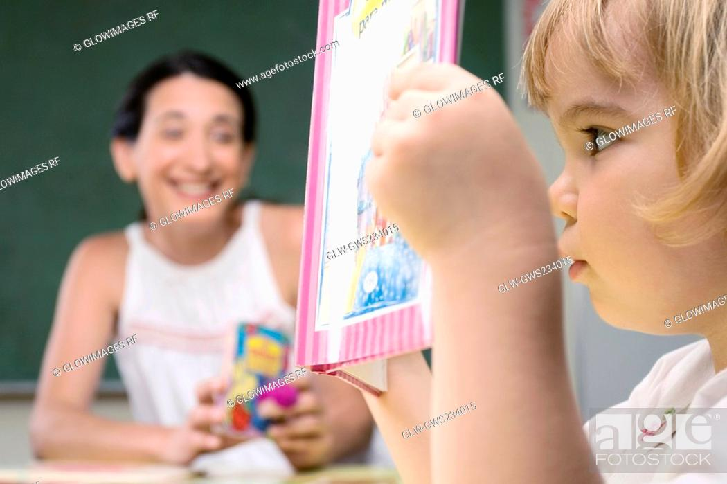 Stock Photo: Close-up of a boy reading a book with his teacher sitting beside him.