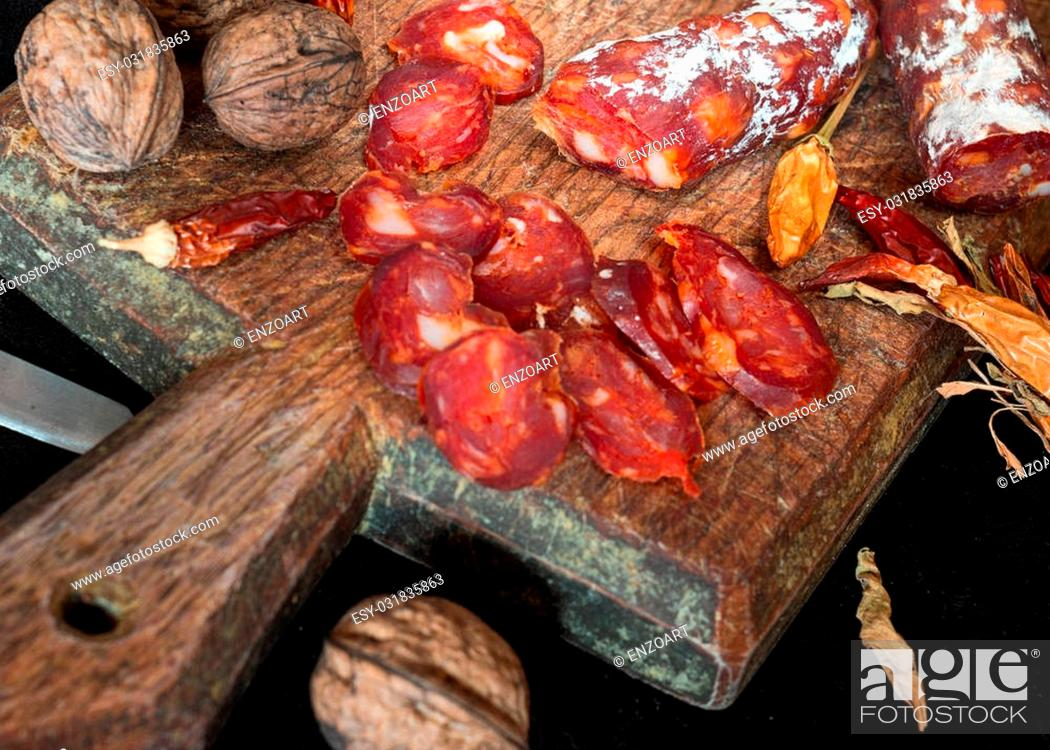 Imagen: Italian sausage and peppers on cutting board with walnuts.