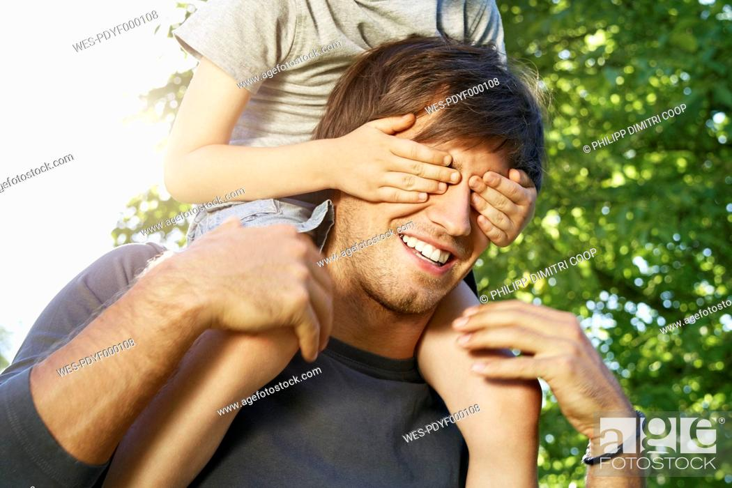 Stock Photo: Germany, Cologne, Father carrying son on shoulders, covering his eyes.
