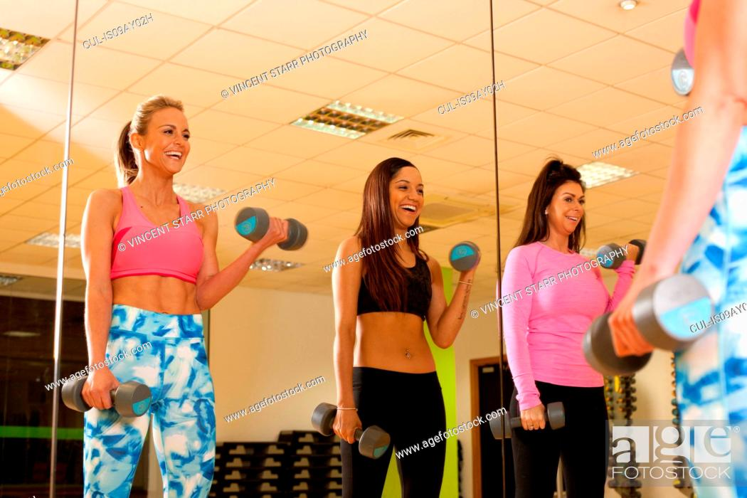 Stock Photo: Mirror image of women in gym using dumbbells.