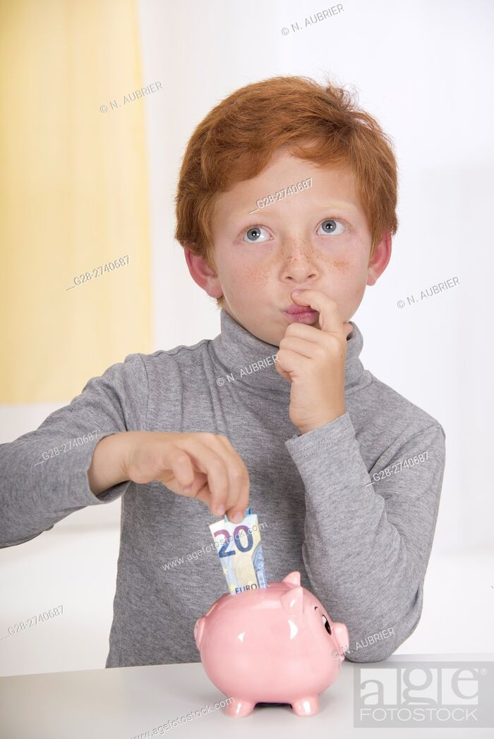 Stock Photo: Little boy with red hair, hesitating before putting a 20 euros banknote into the slot of his pink piggy bank.