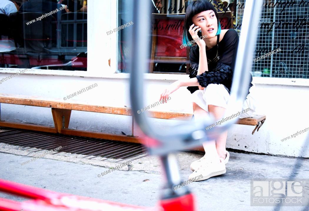 Stock Photo: Young stylish woman sitting outside shop making smartphone call.