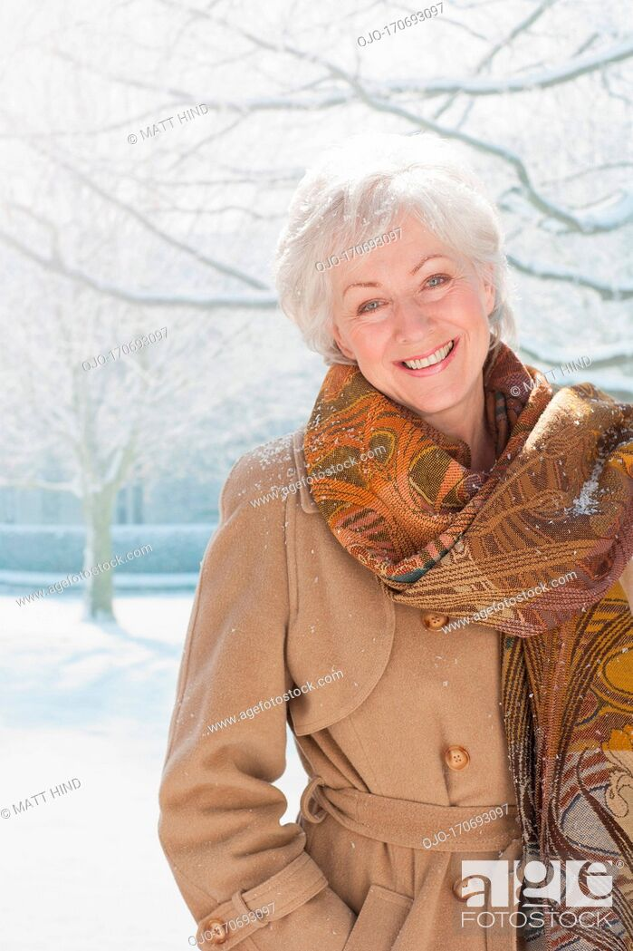 Stock Photo: Snow falling on smiling woman.