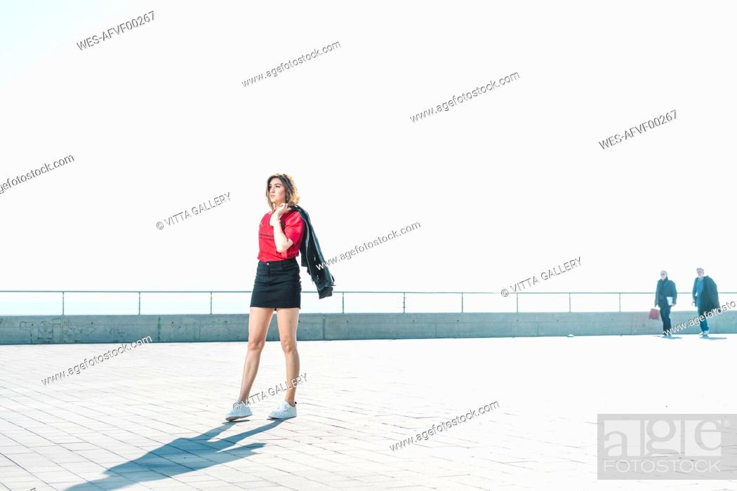 Stock Photo: Fashionable young woman on waterfront promenade.