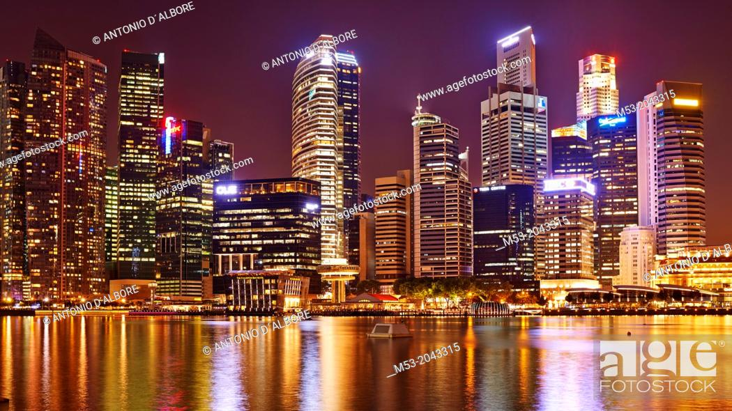 Stock Photo: aerial view of the Central Business District by night. In the foreground the water of Marina bay. Singapore.