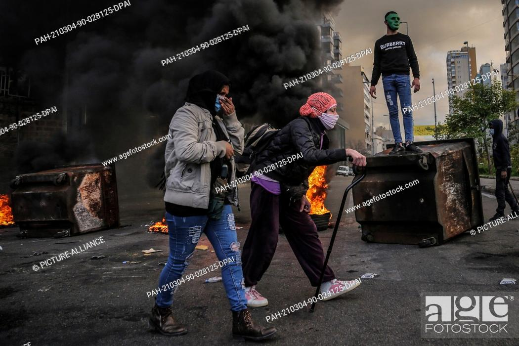 Imagen: 04 March 2021, Lebanon, Beirut: Women walk past burning tires during a protest against Lebanese Lira depreciation against the dollar on the black market due to.