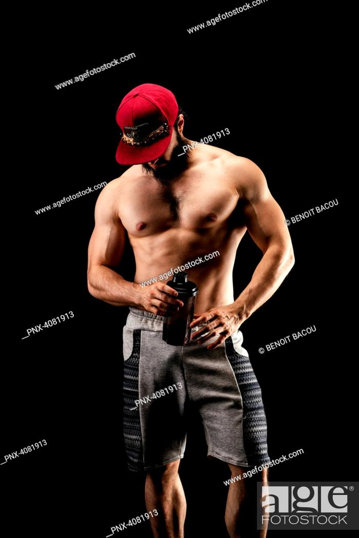 Stock Photo: Bodybuilder Heads Down, A Protein Shaker In Hand.