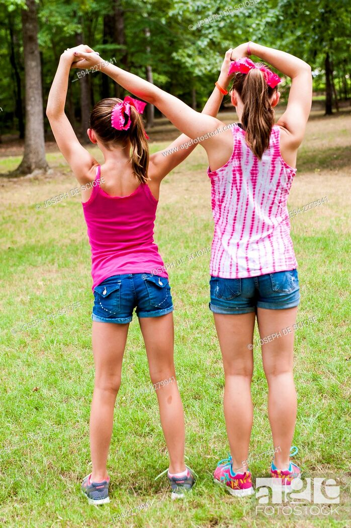 Stock Photo: 2 young sisters, side by side and backs to the camera, with their arms crossing, holding hands.