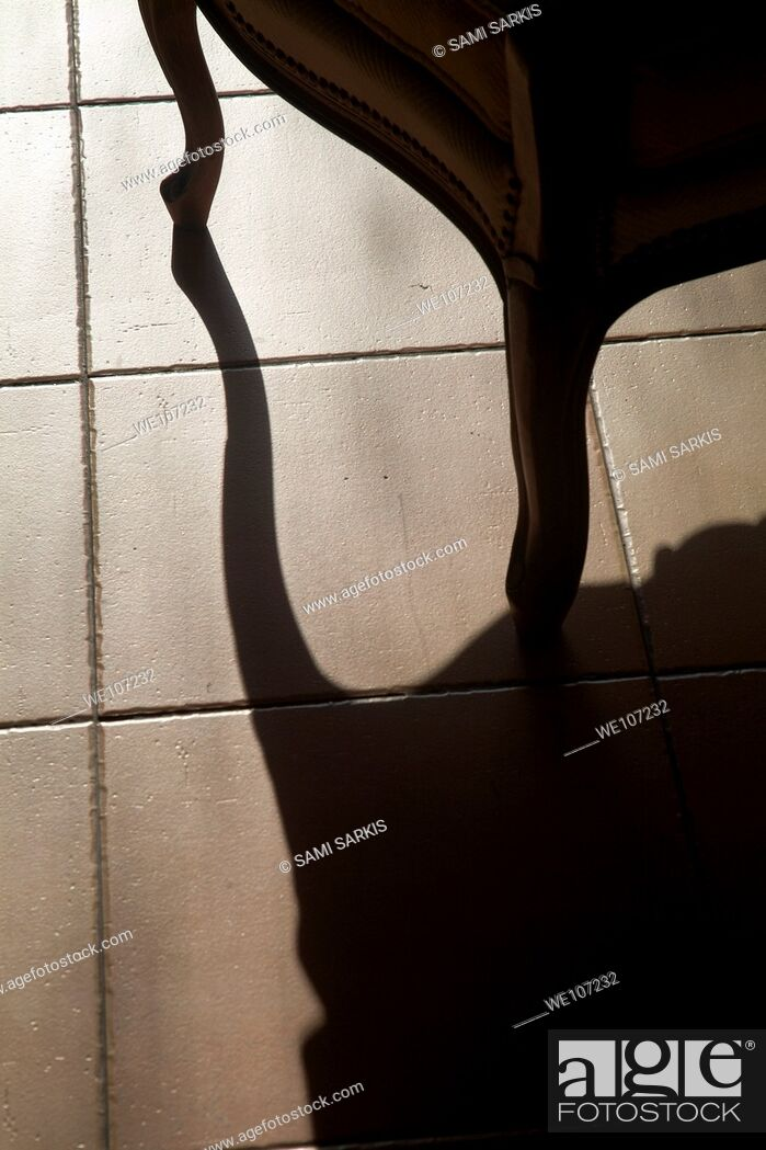 Stock Photo: Shadow of an armchair on a tiled floor.