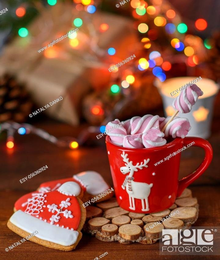 Stock Photo: red ceramic cup with cocoa and marshmallows and baked gingerbread, Christmas lights behind.