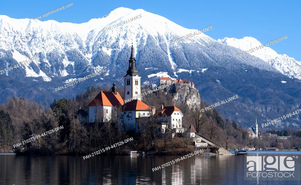 Stock Photo: 15 February 2021, Slovenia, Bled: The Church of the Assumption of the Virgin Mary on the island of Blejski Otok in Lake Bled at the foot of the Pokljuka plateau.