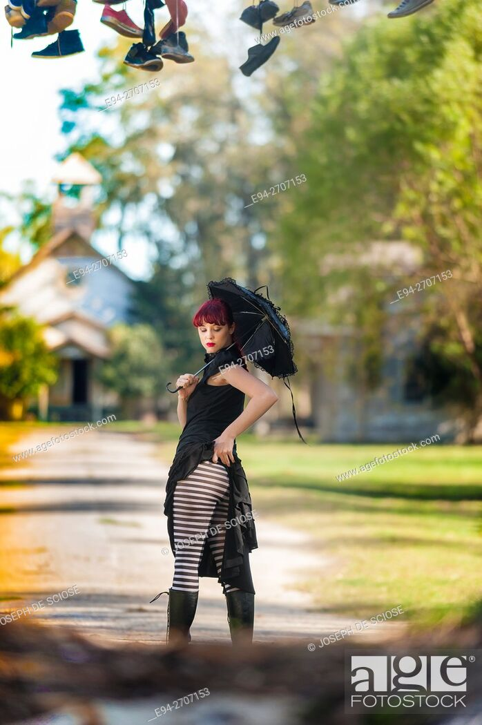 Stock Photo: A pretty 23 year old red headed woman holding a black umbrella and wearing a black dress and striped stockings looking down from the camera, outdoors.