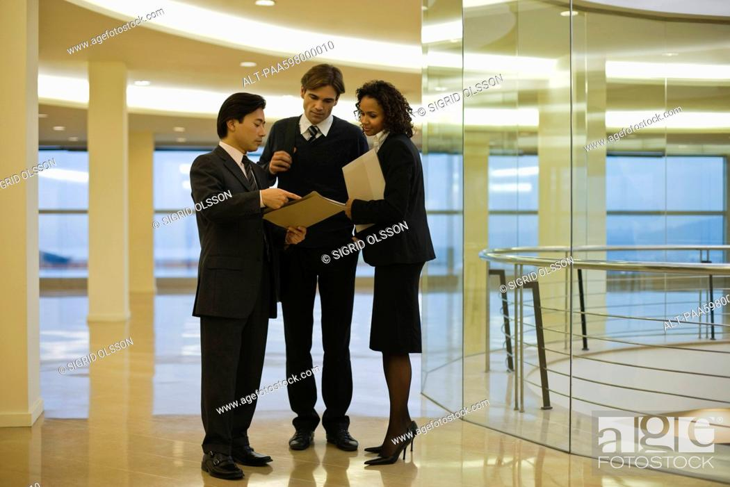 Stock Photo: Business executives standing together discussing document.