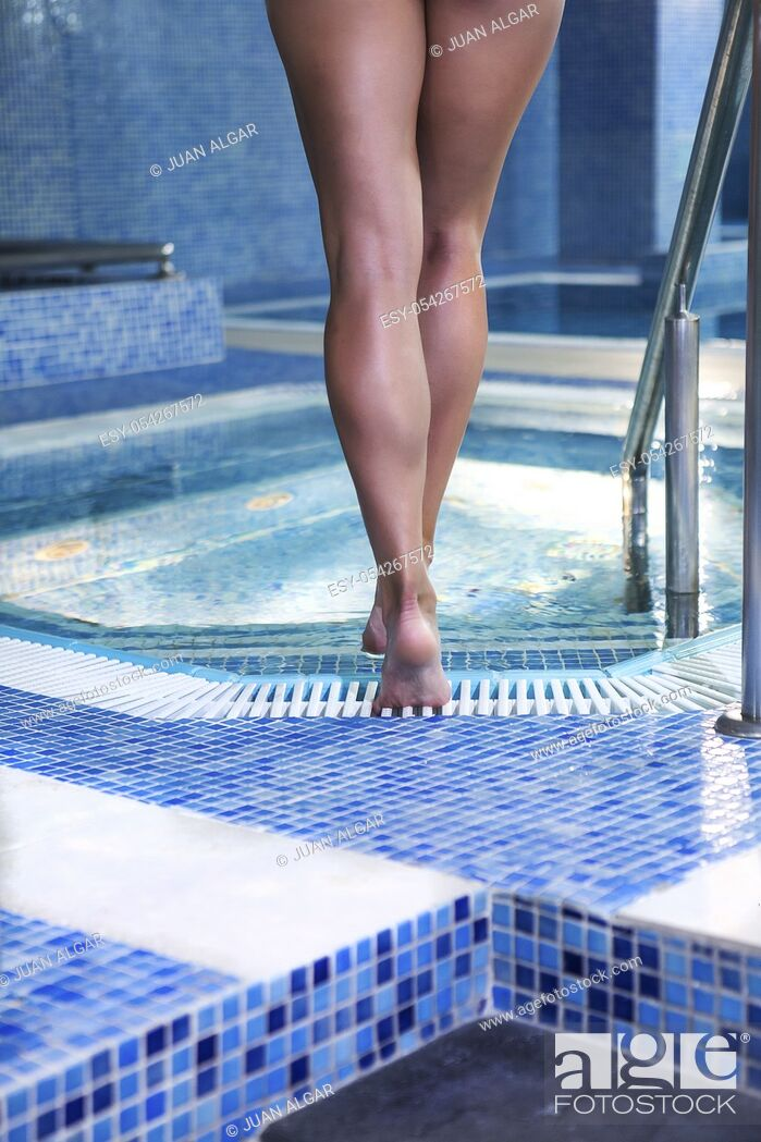 Stock Photo: Back view of female legs walking into pool. Vertical indoors shot.