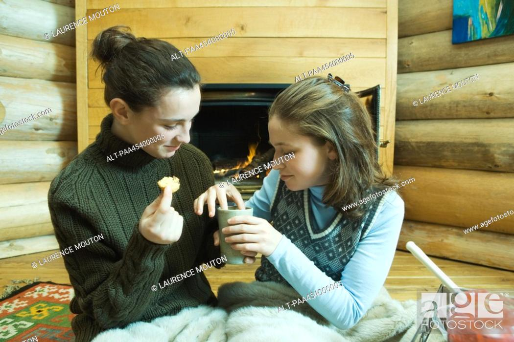Stock Photo: Two teenage girls sitting by fireplace, sharing snack.