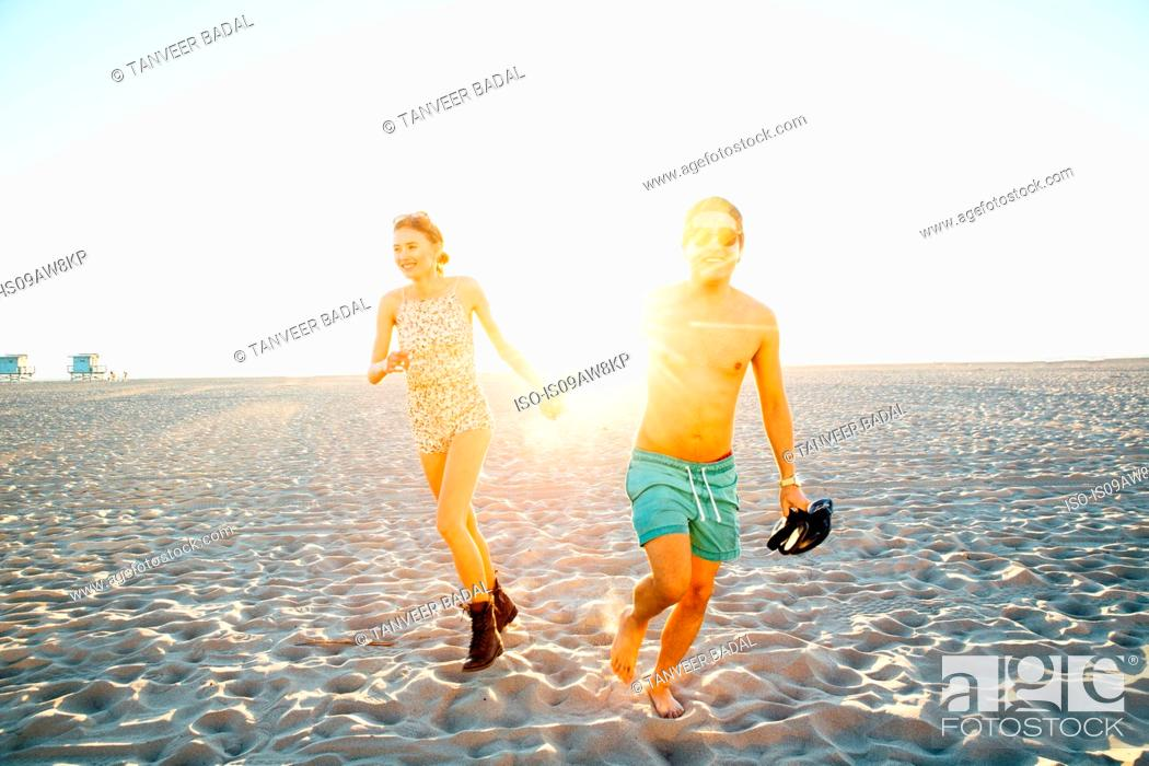 Stock Photo: Young couple wearing swimming costume and shorts running on sunlit beach, Venice Beach, California, USA.