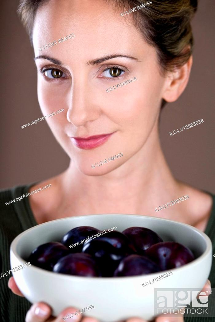 Stock Photo: A mid adult woman holding a bowl of plums.