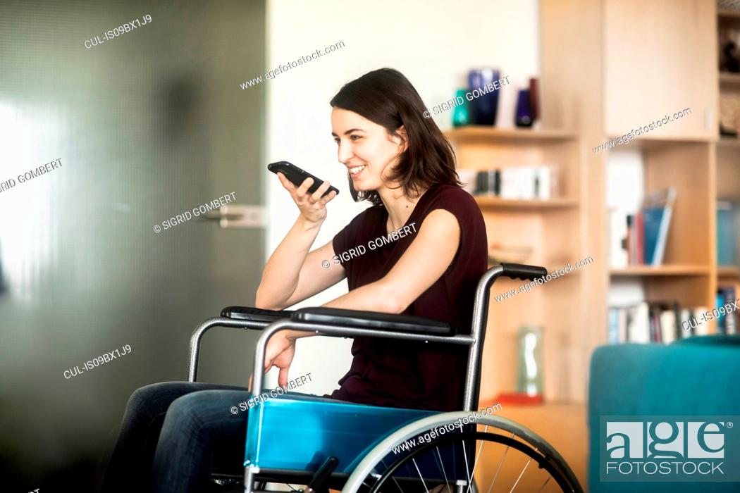 Stock Photo: Woman in wheelchair using cellphone.
