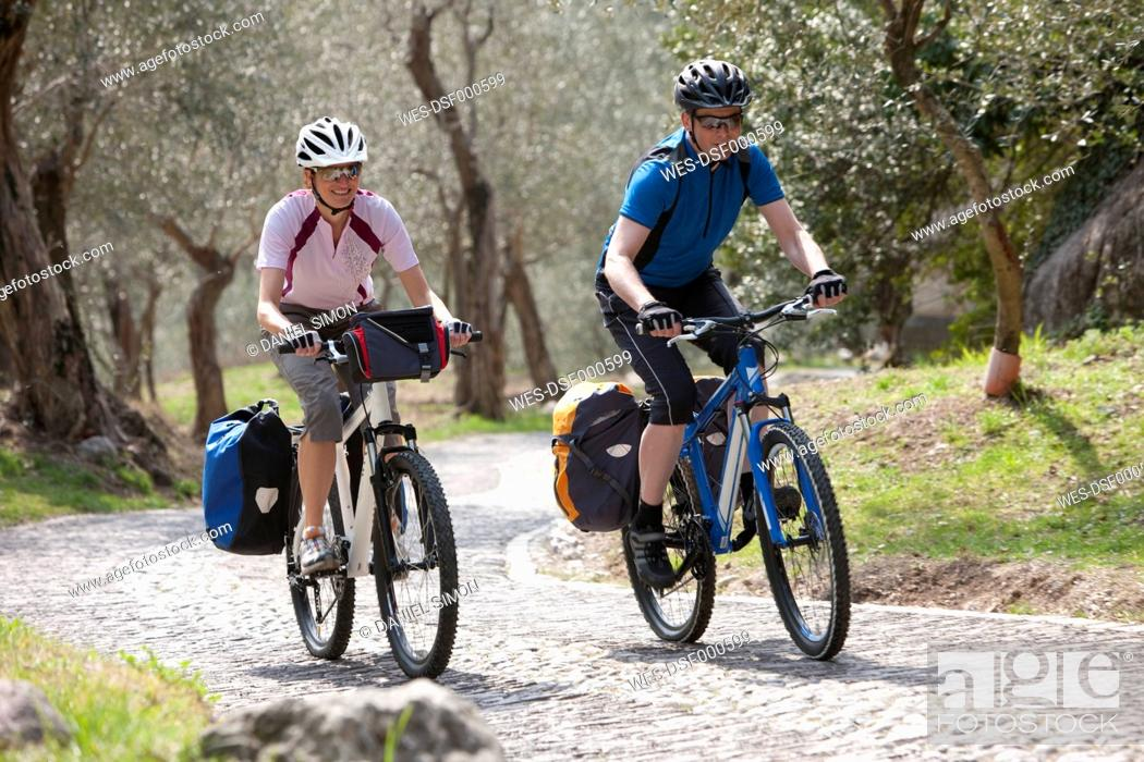 Stock Photo: Italy, Trento, Man and woman cycling through country road.