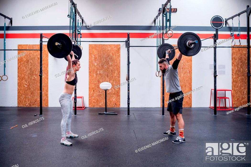 Stock Photo: Young couple lifting barbell in gym.
