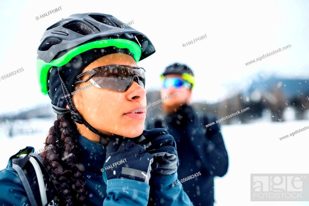 Imagen: Two mountain bikers standing outdoors in winter, putting on helmet.