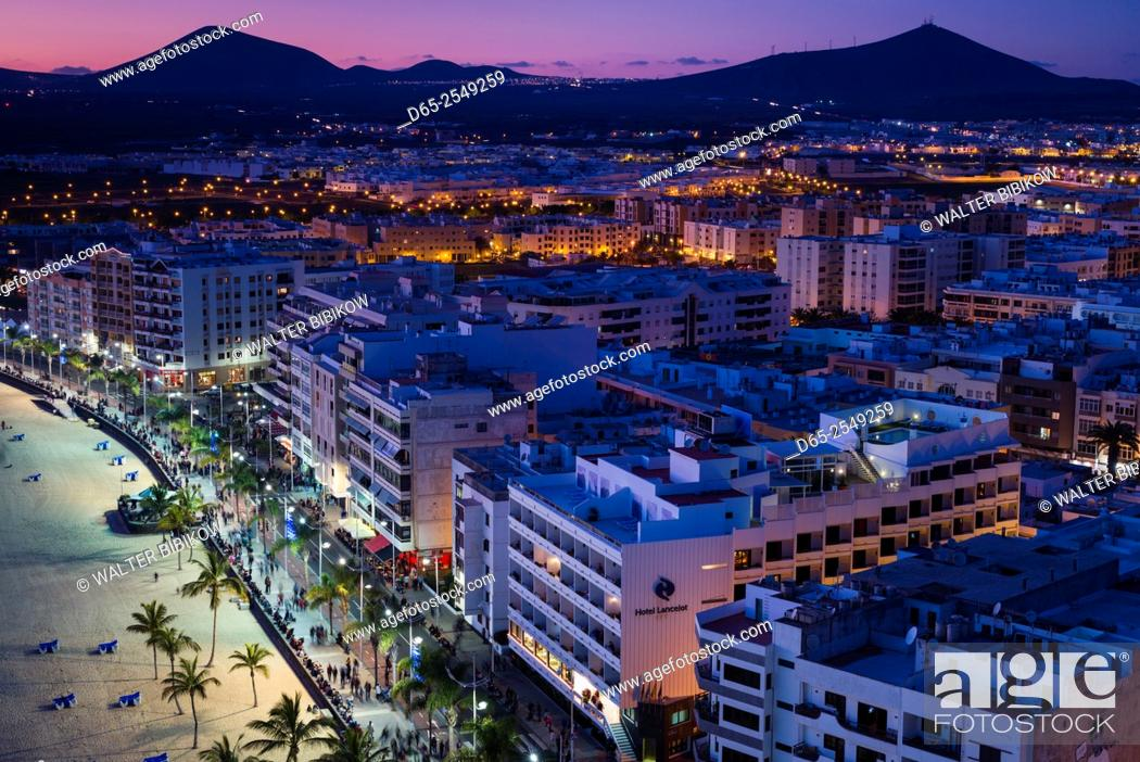 Stock Photo: Spain, Canary Islands, Lanzarote, Arecife, elevated city view above Playa del Reducto beach, dusk.