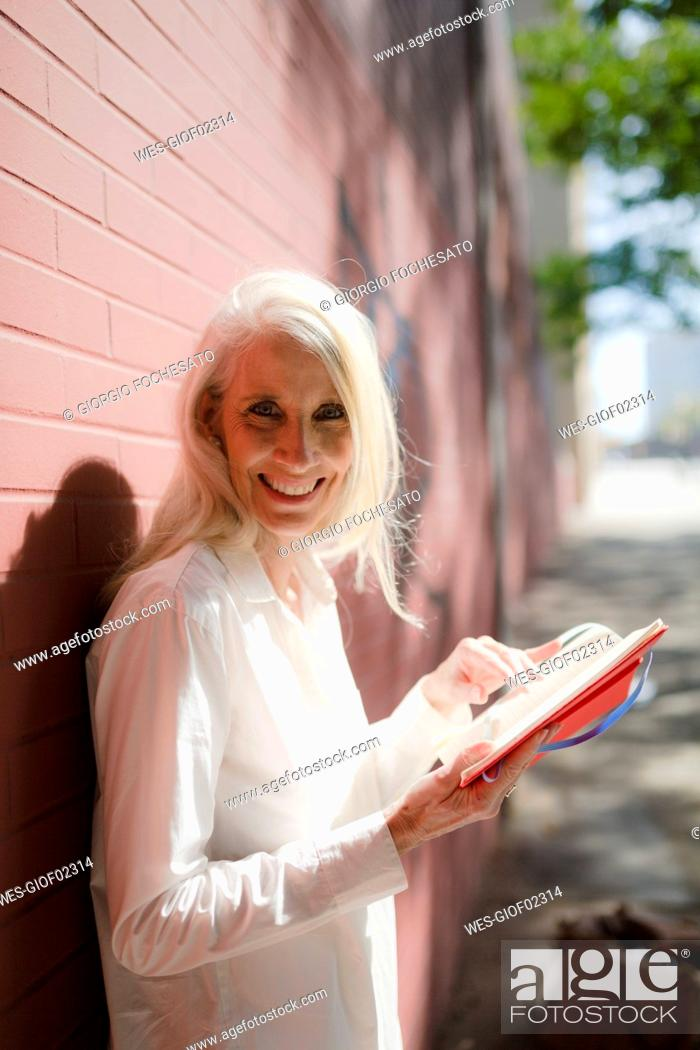 Stock Photo: Portrait of smiling businesswoman with personal organizer.