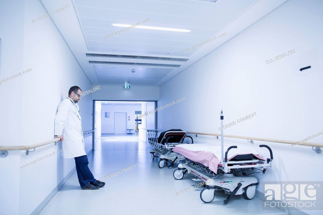 Stock Photo: Worried doctor with head down in hospital corridor.