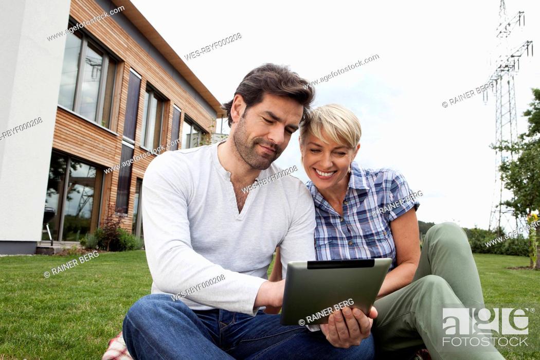Stock Photo: Germany, Bavaria, Nuremberg, Mature couple using digital tablet in garden.