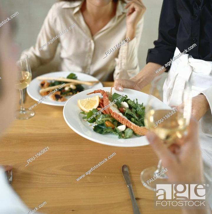 Stock Photo: Waitress serving food for young couple in restaurant.