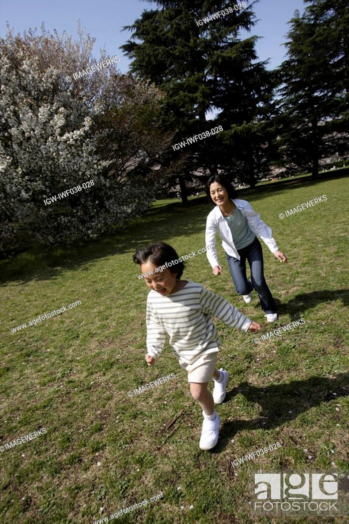 Stock Photo: Mother and daughter playing in a garden.