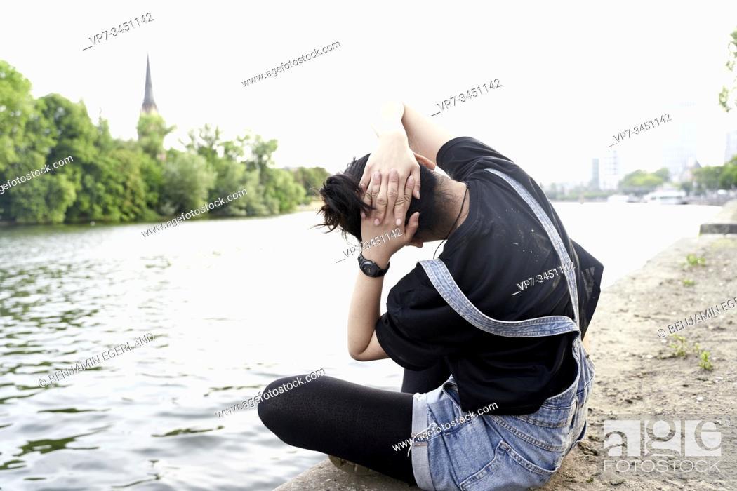 Stock Photo: Korean woman sitting by water, stretching. Frankfurt am Main, Germany.