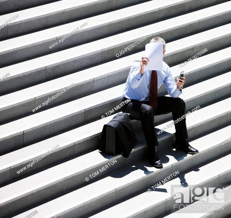 Stock Photo: Businessman sitting on steps looking at paper.
