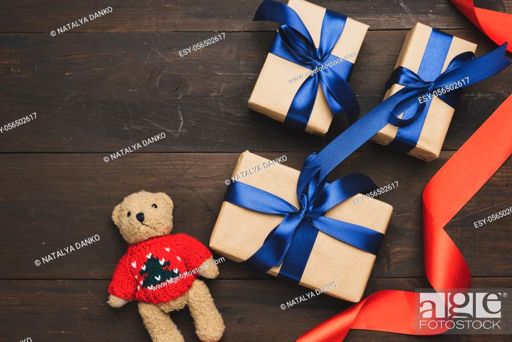 Stock Photo: box wrapped in brown kraft paper and tied with red silk ribbon on brown wooden background, top view.