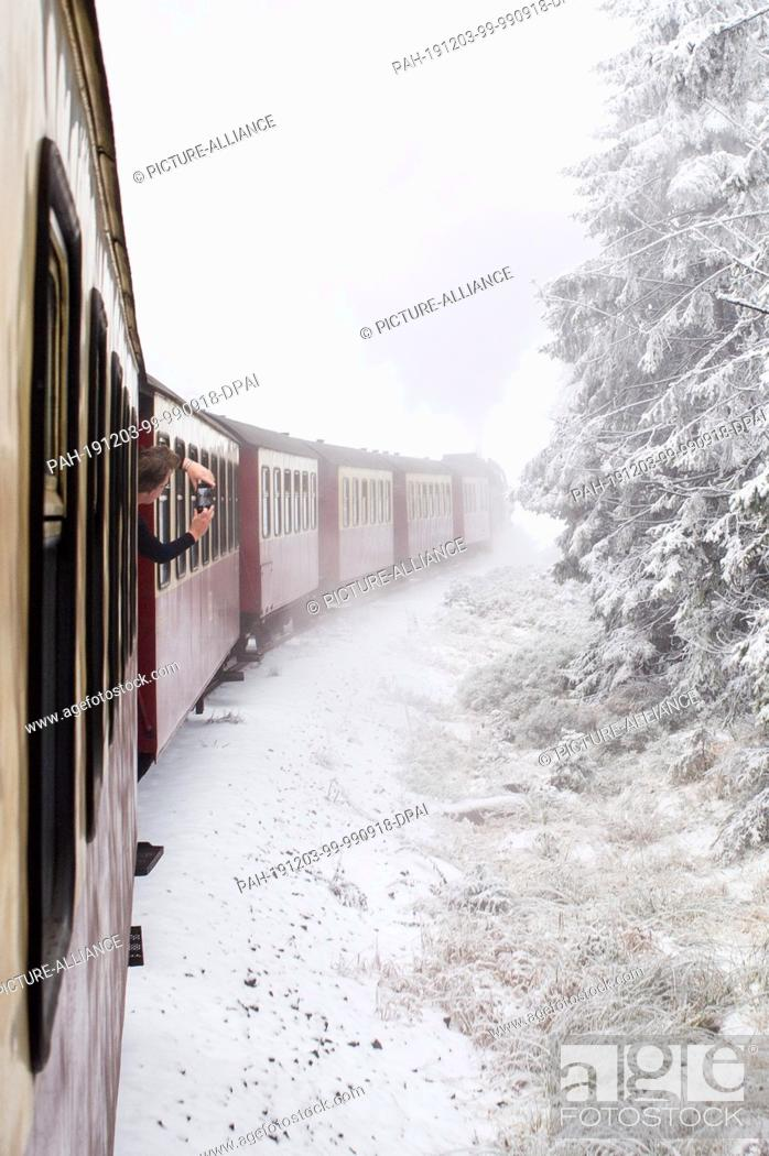Stock Photo: 03 December 2019, Saxony-Anhalt, Wernigerode: A train of the Harzer Schmalspurbahnen (HSB) pulled by a steam locomotive travels through a snow-covered forest.